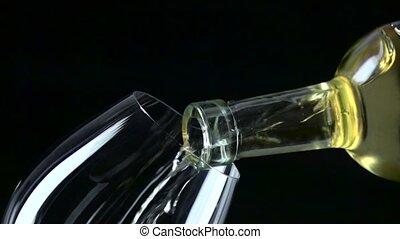 White wine poured into a wineglass, black, closeup, slowmotion