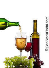 White wine pouring into glass with grape and bottles ...