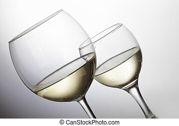 White wine - Two glasses of white wine over light grey...