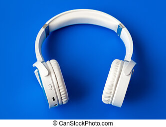 white wireless bluetooth earphones on blue background
