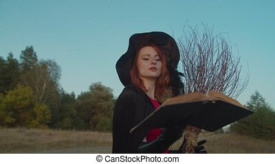 White witch reading magic spell with book at sunset