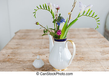White with gold porcelain coffee pot with roses and hyacinths on a wooden tabletop. Clise up