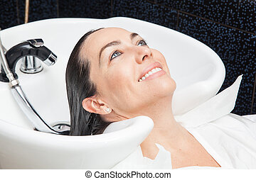 White woman getting a hair wash procedure in a beauty salon