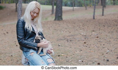 White woman playing with puppy pug outdoors