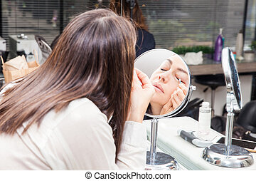 White woman removing makeup in front of mirror at beauty salon