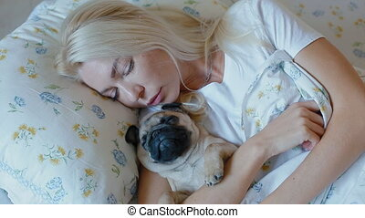 White woman slep in bed with puppy pug