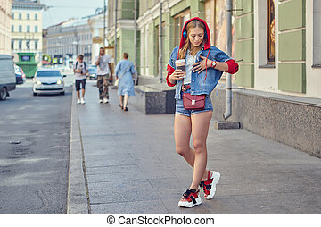 Young woman with coffee cup outdoors. Beautiful caucasian female in fashionable cloth with red hoodie and platform shoes is walking in the city street of Saint-Petersburg center, Russia.