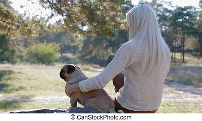 White woman with the pug sitting on the stone in the park...