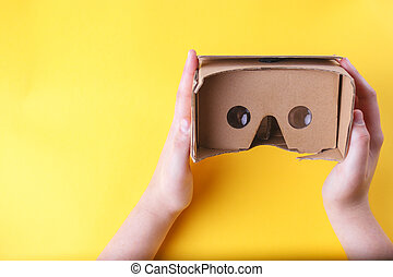 White woman's hands holding cardboard virtual reality glasses