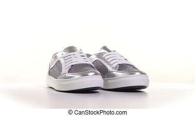 White womens sneakers on a white background. Rotary table