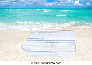 White wood board on the sandy beach