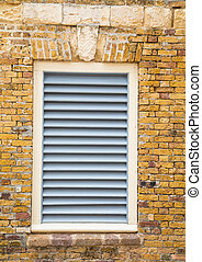 White Wood Shutters in Old Brick Wall
