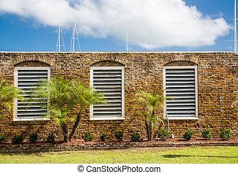 White Wood Slat Windows in Old Stone Wall