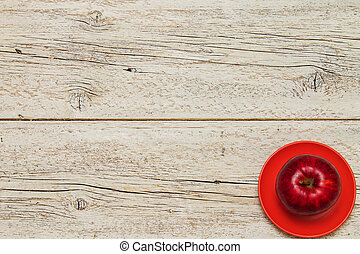 white wooden background with a red apple