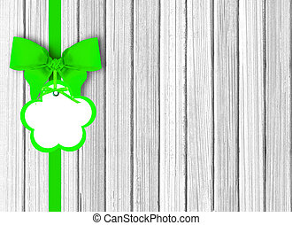 white wooden background with beautiful green bow with tag