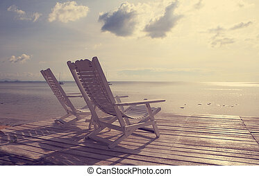 White wooden beach chair facing seascape, vintage filter effect