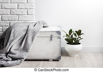 White wooden box with gray soft fleece blanket on it and young rubber plant in white flower pot