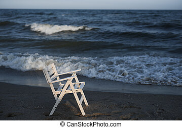White wooden chair on the beach. Empty beach, sunset, cold weather and the sea.