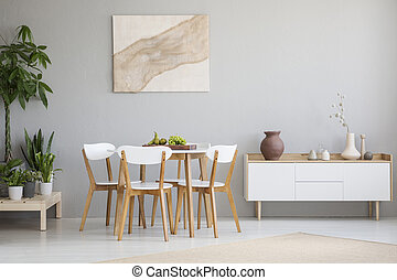 White wooden chairs at table between plants and cupboard in grey flat interior with poster. Real photo