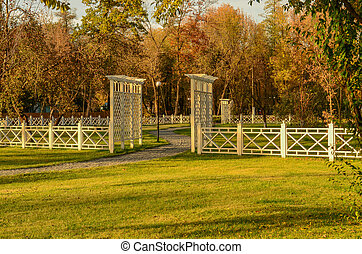white wooden fence and green lawn in the autumn park