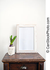 White wooden frame on a dark bedside table