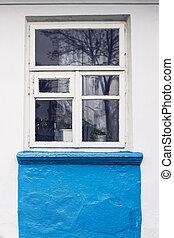 White wooden frame window in old Ukrainian village house