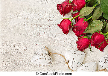 White wooden hearts and red roses on white wooden background, top view