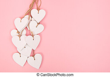 White wooden hearts on a pink background with space for text