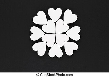 White wooden hearts on black background