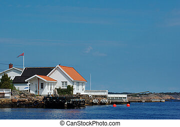 White wooden house with jetty in Lyngor along the Southern-Norwegian coast