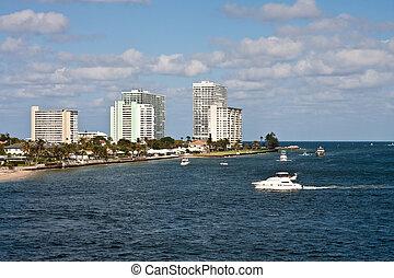 White Yacht Cruising Past Luxury Condos on the Coast