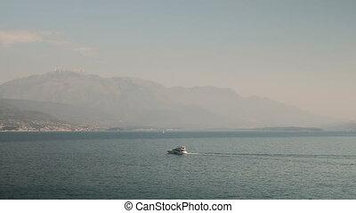 White yacht moves along sea towards city.