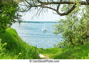 white yacht on water in natural green frame