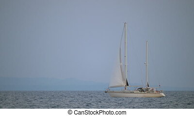 White yacht sailing in quiet sea - Scene with quiet blue...
