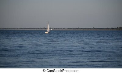 White yacht with sails moves on blue water