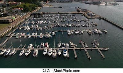 white yachts at the berths in the seaport, aerial view from a drone