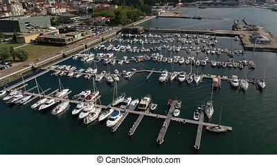 white yachts at the berths in the seaport, aerial view from drone