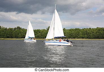 white yachts sail in the lake , Mazury, Poland