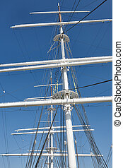 White yatch masts over a blue sky. Nautical background