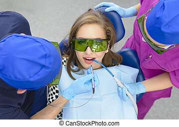 Whitening Laser - Dentist using whitening laser on a female ...