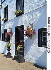 Whitewashed building with flowers in the village of Inveraray Scotland by Loch Fyne