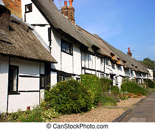 A row of whitewashed thatched cottages in a Buckinghamshire village