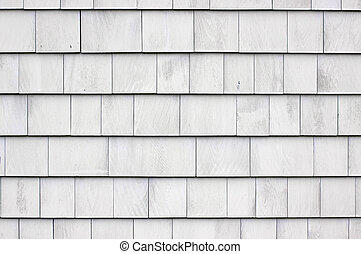Close view of a wall that has whitewashed wood shingles.