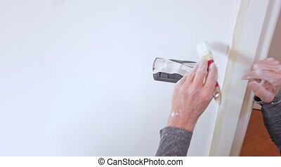 Whitewasher with paintbrush in white on a blank wall.