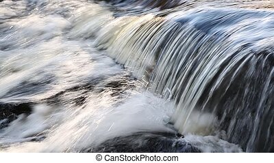 Whitewater Flow Loop - Whitewater splashes over rocks in...