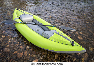 whitewater inflatable kayak on a river