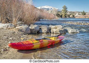 whitewater kayak on river shore - whitewater kayak with a ...