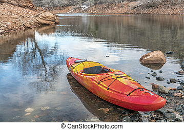 whitewater kayak on rocky shore - colorful river kayak on a...
