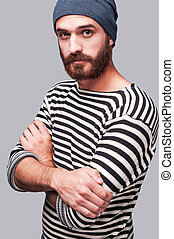 Who is the man? Confident young bearded man in striped clothing keeping arms crossed and looking at camera while standing against grey background