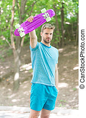 Who want to learn extreme trick. Guy carries penny board ready to ride. Man serious face carries penny board park nature background defocused. Man likes to ride skateboard and sporty lifestyle